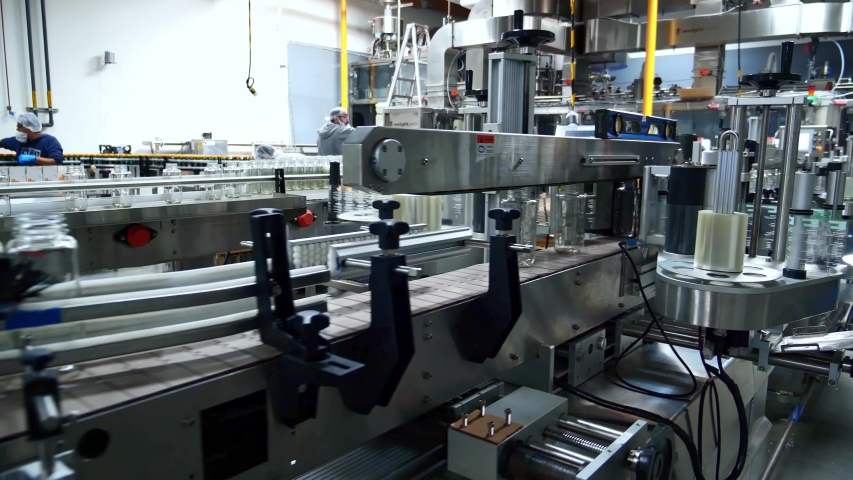 Automation line for bottling juice into glass bottles. Industrial juice factory indoors machinery. Robotic production line. Beverage factory interior. Royalty-Free Stock Footage #1055188598