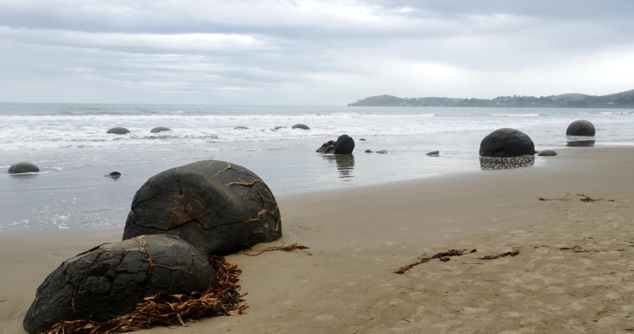 The Moeraki Boulders are unusually large and spherical boulders lying along a stretch of Koekohe Beach on the wave-cut Otago coast of New Zealand  | Shutterstock HD Video #1055191646