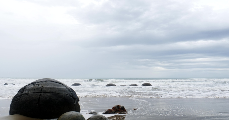 The Moeraki Boulders are unusually large and spherical boulders lying along a stretch of Koekohe Beach on the wave-cut Otago coast of New Zealand  | Shutterstock HD Video #1055191649