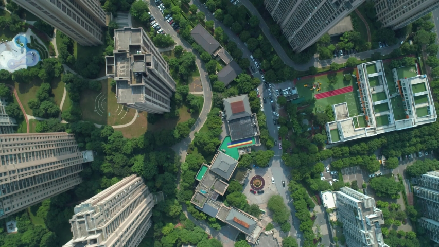 Aerial drone shot over residential apartment buildings on sunny day. Aerial shot over community apartment complex in China.