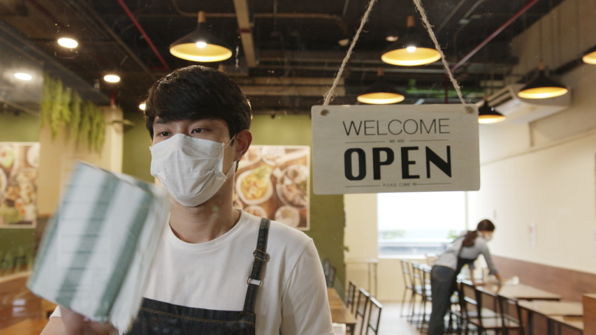 Business reopen again concept asian man working in a restaurant turning open sign at front to open after lockdown and epidemic of coronavirus covid-19