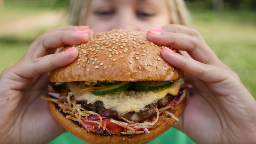Pretty young woman is eating appetizing hamburger on the street. Close-up | Shutterstock HD Video #1055200088