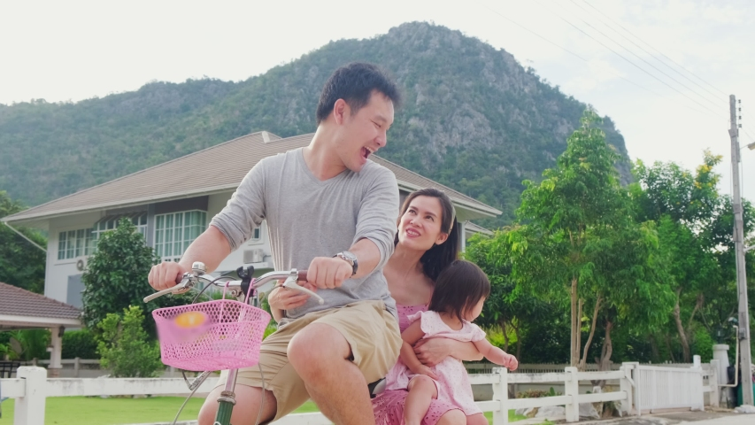 Asian family ride a bicycle and having fun together. Father bike, mother holding baby child on back seat talking and laughing. Parents and daughter activity, kid feeling happy with big smile on face.