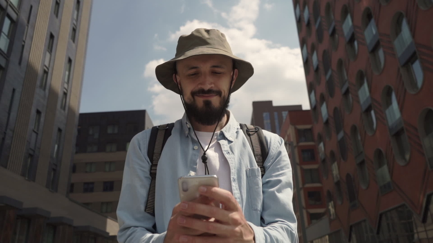 Tourist man travels around the city. The traveler guy with a backpack and a hat uses a smartphone to communicate. Hipster with a beard smiles while looking at the phone. Technology urban environment. | Shutterstock HD Video #1055204408