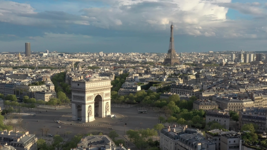France, Paris Arc de Triomphe (Triumphal Arch) in Champs Elysees and Eiffel tower behind, at sunset (or sunrise). 4k Quality drone shot, aerial view from right to left (helicopter or drone shot)