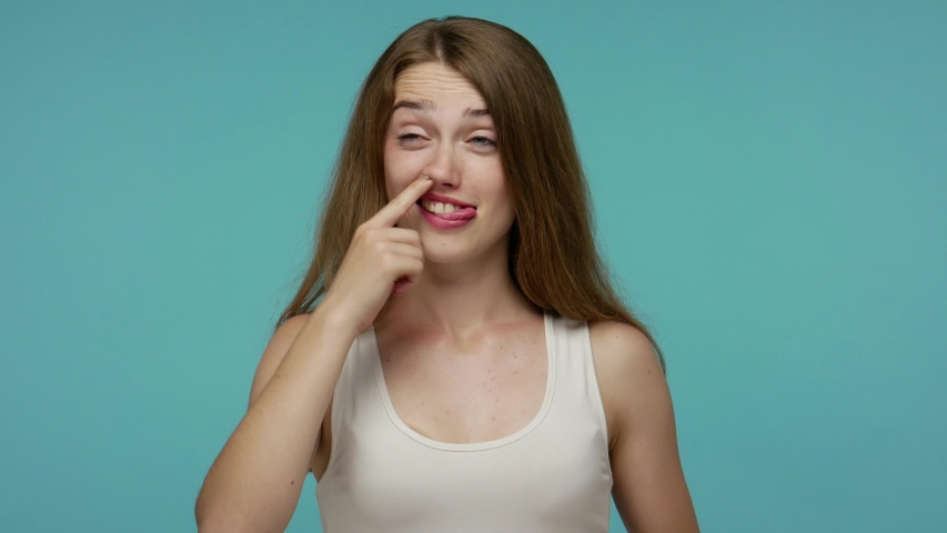 Funny stupid carefree girl picking nose and sticking out tongue with silly brainless humorous expression, removing boogers, uncultured habit, bad manners. studio shot isolated on blue background