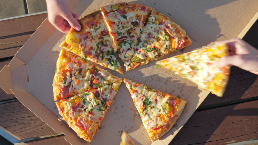 Human hands take slices of fresh pizza from an open box. Friends enjoy food in a city park. The concept of catering and delivery services Royalty-Free Stock Footage #1055208671