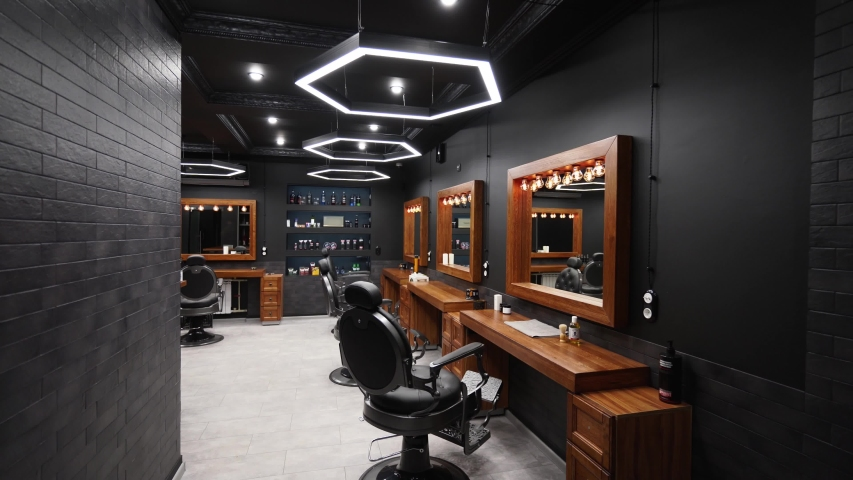 Vintage barbershop interior - movement along the chairs, wooden tables and mirrors. Stylish hair studio indoors. Stylish beauty salon design with modern lighting and lamps. Royalty-Free Stock Footage #1055208863