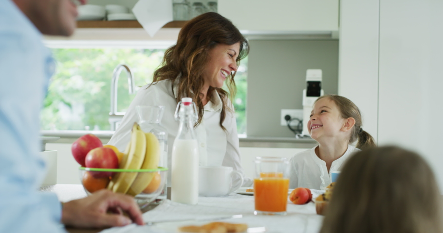 Authentic shot of a happy smiling family is enjoying their time together while having a breakfast in a kitchen at home in the morning. Royalty-Free Stock Footage #1055209310