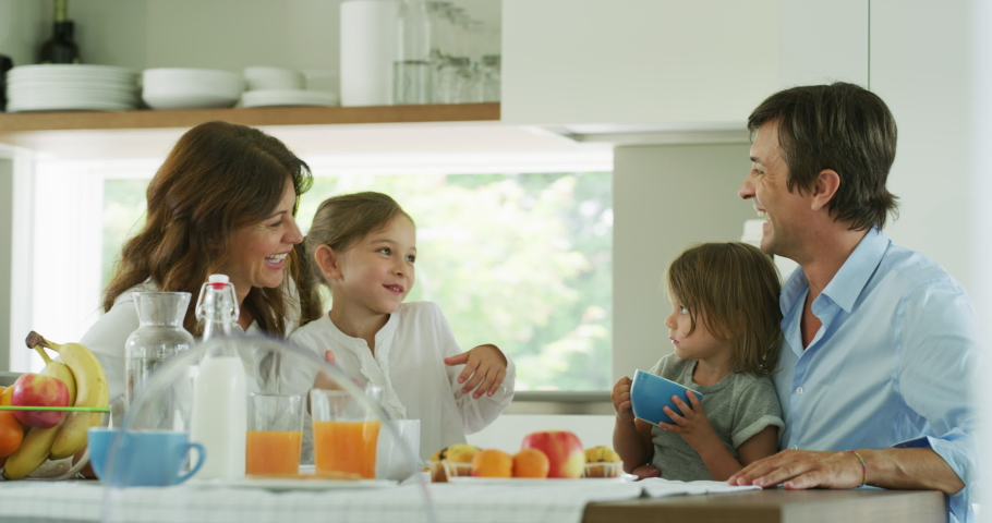 Authentic shot of a happy smiling family is enjoying their time together while having a breakfast in a kitchen at home in the morning. Royalty-Free Stock Footage #1055209313