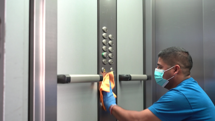 Cleaning professional thoroughly disinfecting elevator push buttons Royalty-Free Stock Footage #1055210621