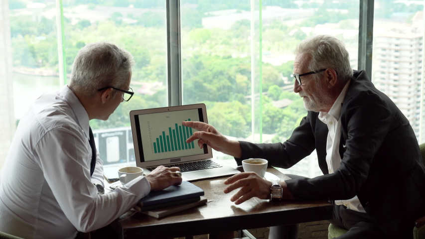 Two senior businessman in meeting pointing graph in laptop analyzing  data information. old man ceo discussing with client in cafe. serious mature manager talking by window over cityscape luxury