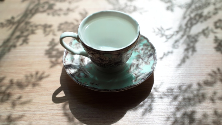 Pouring water out of the beautiful cup. The Cup is emptied. Beautiful shadow on the table. Top view. Revers effect.