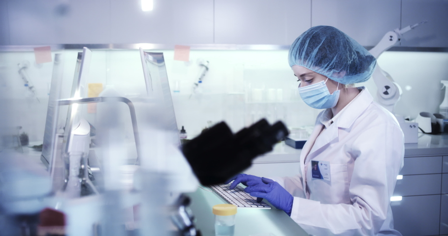Multi ethnic female microbiologists studying virus samples. Research partner in background | Shutterstock HD Video #1055215691