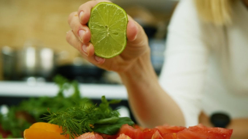 Female hand squeezing juice of half a lime. Woman creates a plate of healthy food. Healthy lifestyle concept