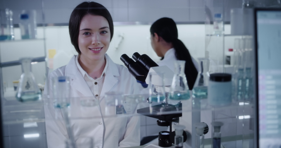 Microbiologist during research. Using microscope and looking at camera | Shutterstock HD Video #1055216651
