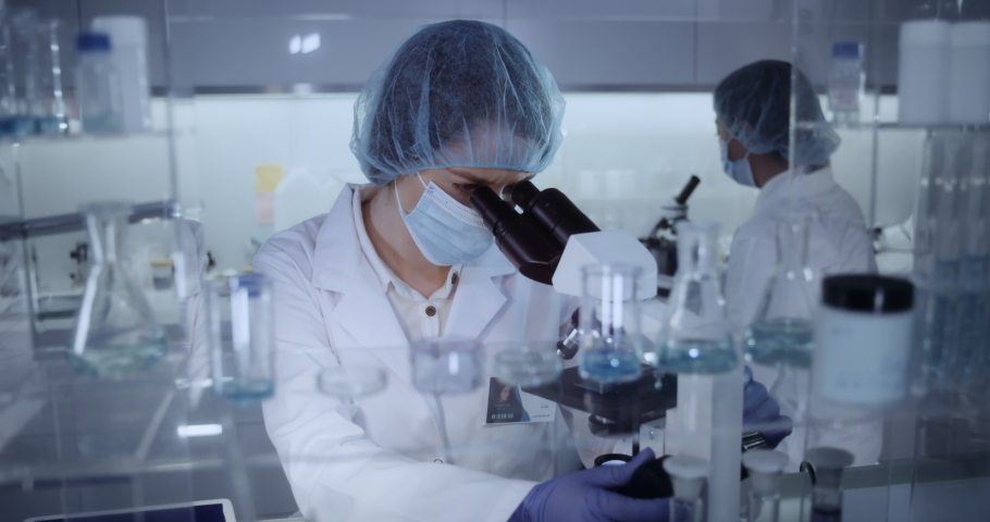 Multi ethnic, female team studying DNA mutations. Wearing protective workwear. Computer screens with DNA Royalty-Free Stock Footage #1055216804