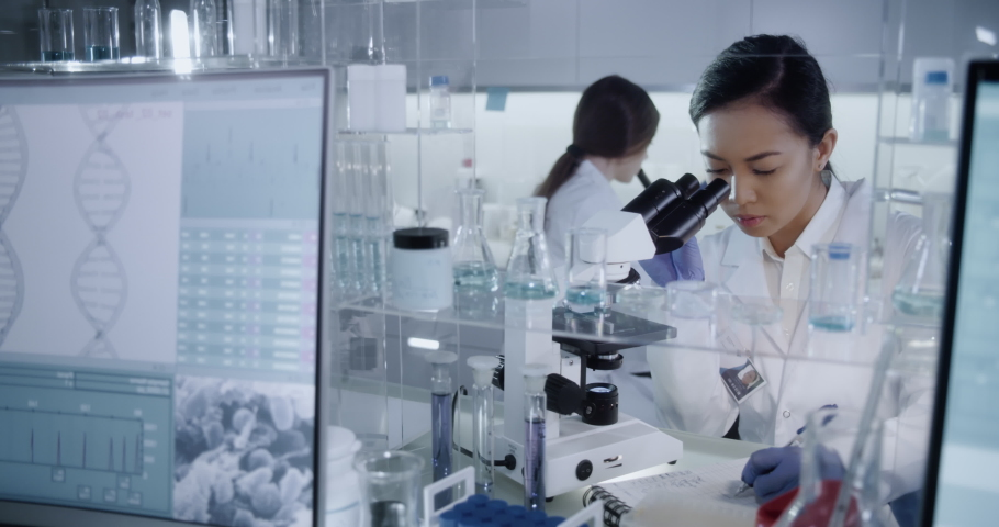 Multi ethnic, female team studying DNA mutations. Wearing protective workwear. Computer screens with DNA | Shutterstock HD Video #1055216810