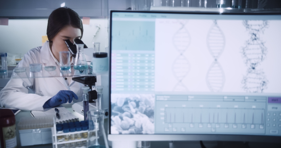 Multi ethnic, female team studying DNA mutations. Wearing protective workwear. Computer screens with DNA | Shutterstock HD Video #1055216822