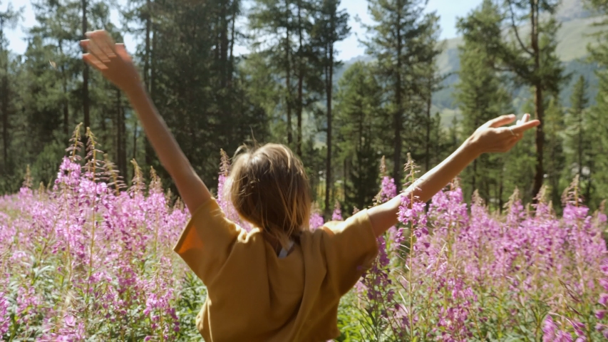 Young woman arms open in flower field enjoying freedom in nature embracing life and balance. Girl arms outstretched in purple flowers in sunshine light. Slow motion  Royalty-Free Stock Footage #1055222666