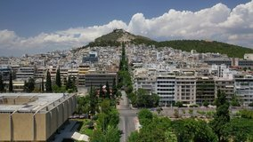 Aerial drone video of Athens urban dense populated cityscape leading to iconic Lycabettus hill and uphill church of Saint George, Attica, Greece