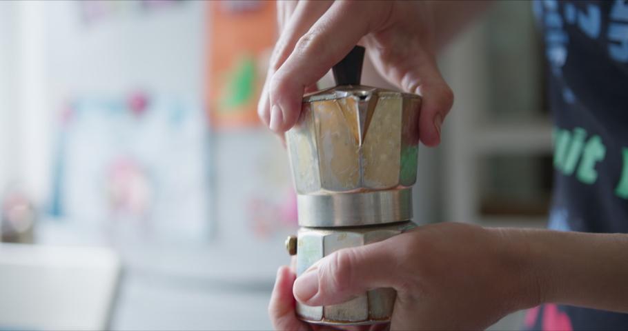 Woman prepares coffee in the Mocha coffee maker | Shutterstock HD Video #1055226035