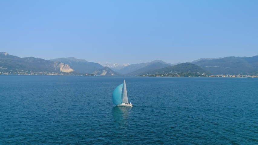 Drone shot of epic romantic sailboat with full sail of wind. Beautiful private yacht on amazing italian mountain lake, summer vacation on boat   Shutterstock HD Video #1055226320