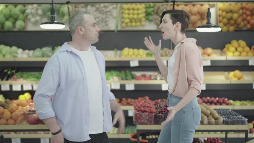 Side view of nervous man and woman arguing emotionally in grocery. Portrait of argued Caucasian family quarrelling in food shop. Conflict, marriage and relationship problems, buying.