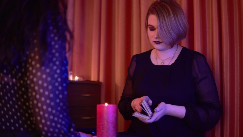 Witch or fortune teller with customer, gypsy reading tarot card future, mystic medium paranormal ritual | Shutterstock HD Video #1055231588