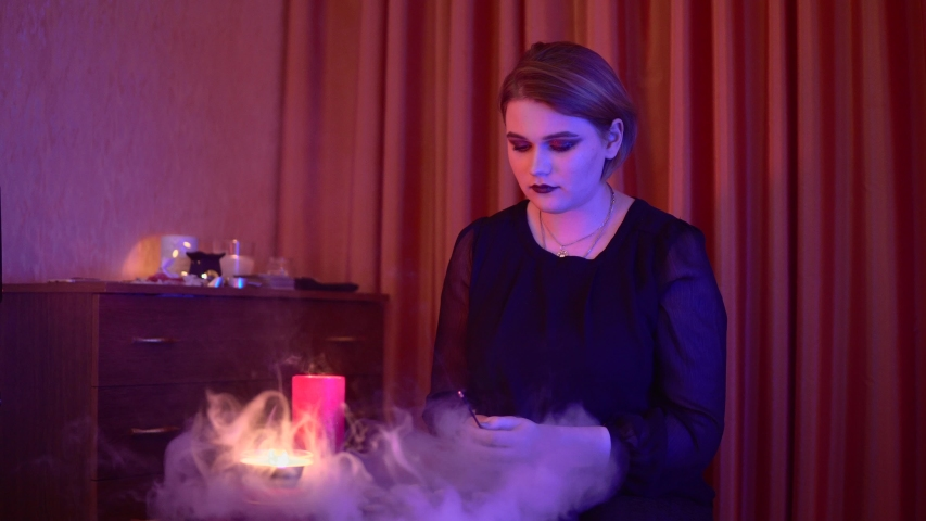 Woman witch with aroma sticks, ritual candles and runes, future teller occult esoteric magic ritual | Shutterstock HD Video #1055232158
