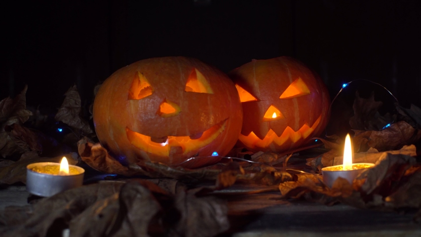 Halloween, two pumpkins with a scary luminous face inside, candles are burning and light is playing, changing. | Shutterstock HD Video #1055234555