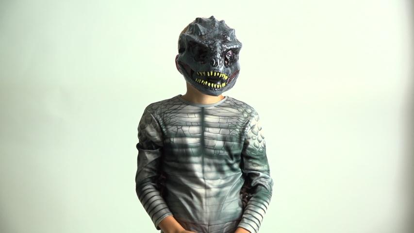Little Boy in Dinosaur Costume Holding out a Jack O Lantern Candy Bucket | Shutterstock HD Video #1055239169