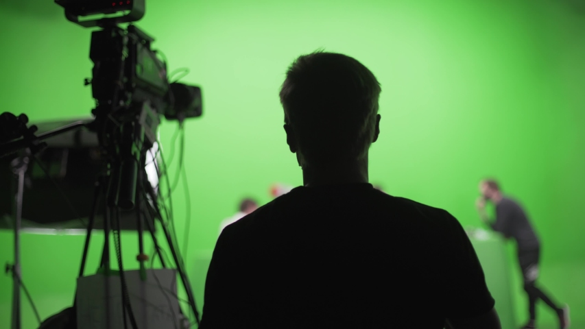 Film crew in green studio shooting video. Chroma - technology of combining two or more images or frames in single composition. Cameraman,director,crew. Filmmaking industry.