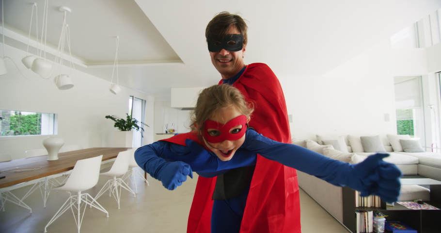 A carefree happy smiling father and daughter dressed as superheroes are having fun to run and jump while playing an imagination game at home. | Shutterstock HD Video #1055239961