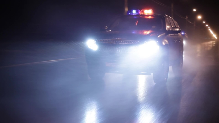 Three police cars in high speed pursuit. Emergency response police patrol vehicle speeding to scene of crime at night and rain. Outdoor front view of police traffic auto driving.
