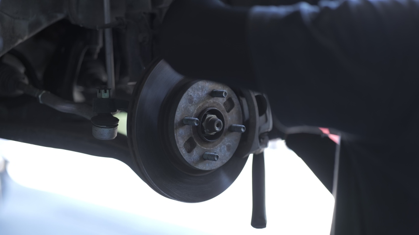 The mechanic is putting the brake disc to the car.   Shutterstock HD Video #1055240984