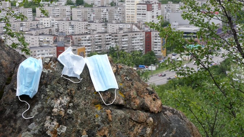 Three discarded used disposable medical masks lie on a large stone on the background of the city.   Shutterstock HD Video #1055243972