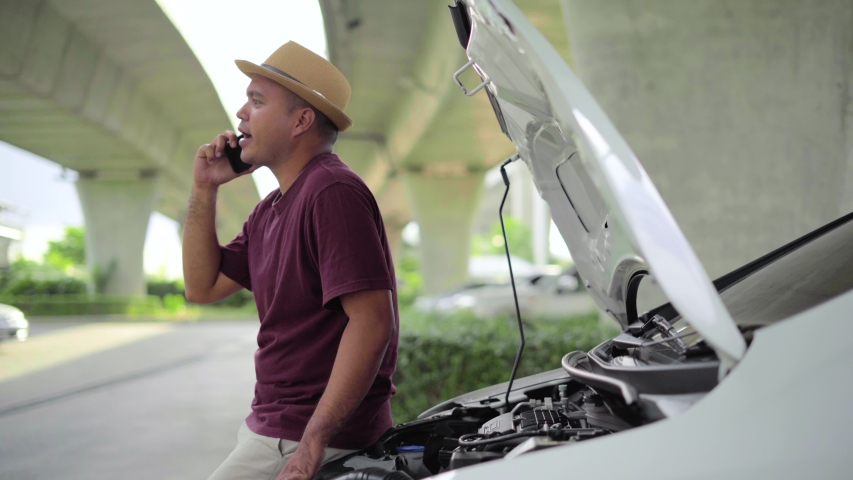 Asian man has  broken down car on the road he talking on phone to call someone to help or mechanics car service. 4k resolution shot.   Shutterstock HD Video #1055244662