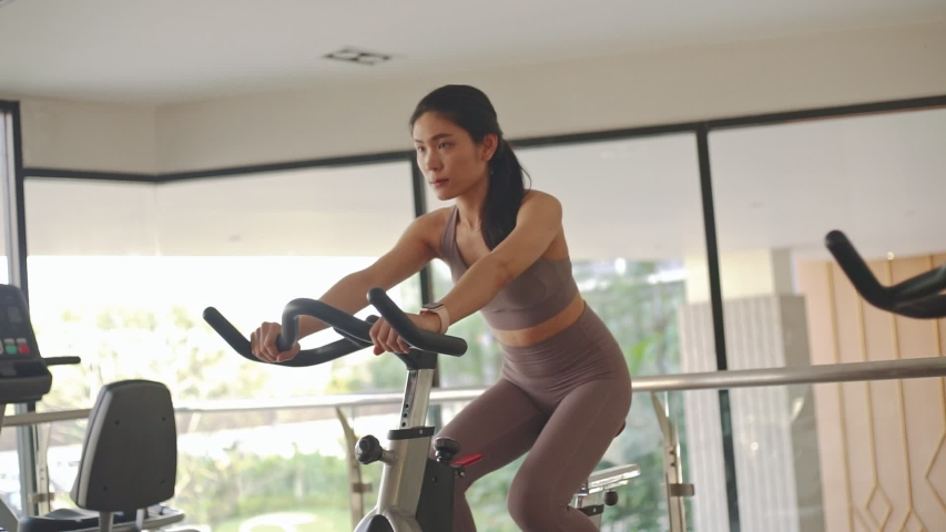 Beautiful young Asian woman doing cardio on a exercise bike at gym | Shutterstock HD Video #1055244716