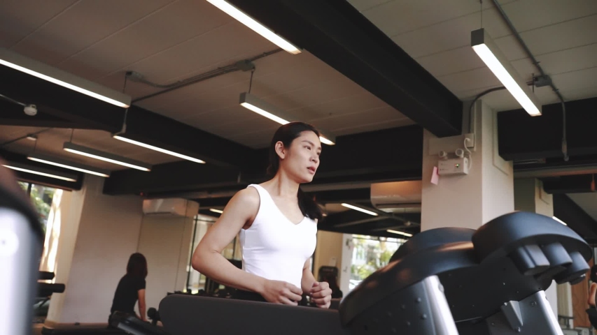 Young sports woman is running treadmill in gym. Doing cardio training | Shutterstock HD Video #1055244722