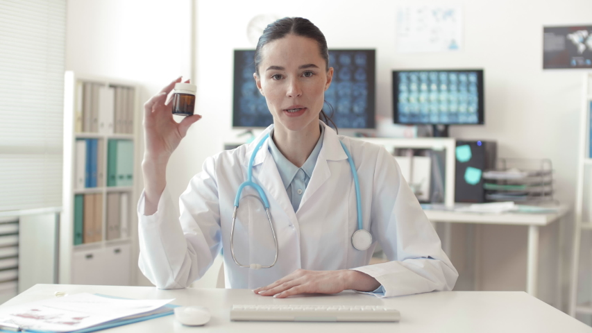 Lockdown portrait of young female physician wearing medical overall and stethoscope sitting in front of computer, holding medicine and prescribing it to online patient | Shutterstock HD Video #1055244959