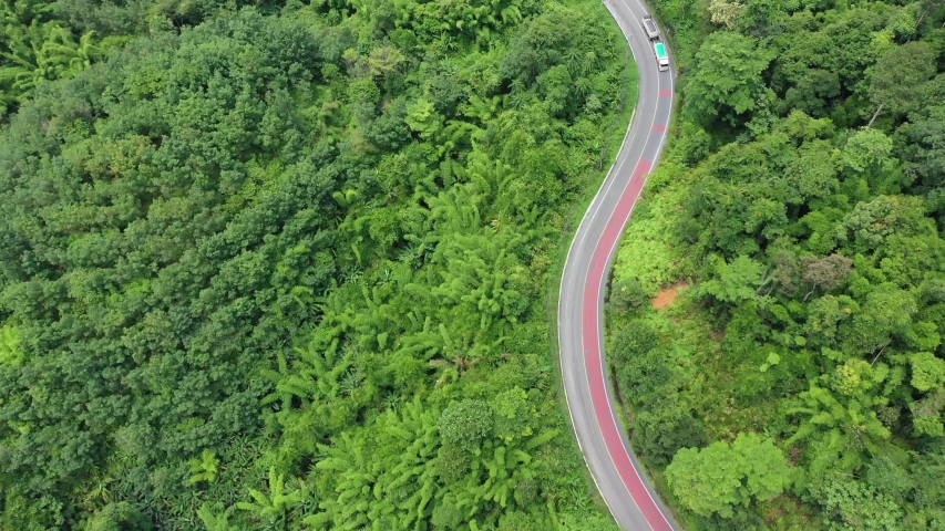 Scenic road through forest with traffic driving. Aerial footage of cars and trucks on journey through countryside   Shutterstock HD Video #1055245664