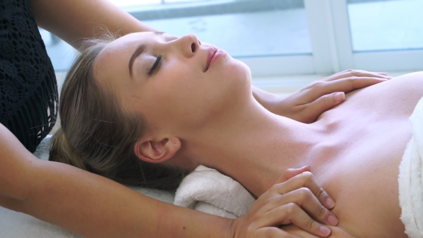 Relaxed woman getting shoulder massage in luxury spa by professional massage therapist. Wellness, healing and relaxation concept. | Shutterstock HD Video #1055245772