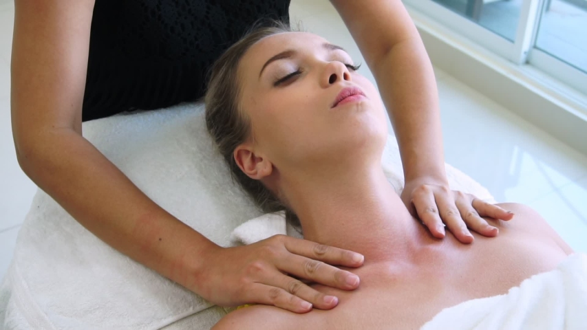 Relaxed woman getting shoulder massage in luxury spa by professional massage therapist. Wellness, healing and relaxation concept. | Shutterstock HD Video #1055245784