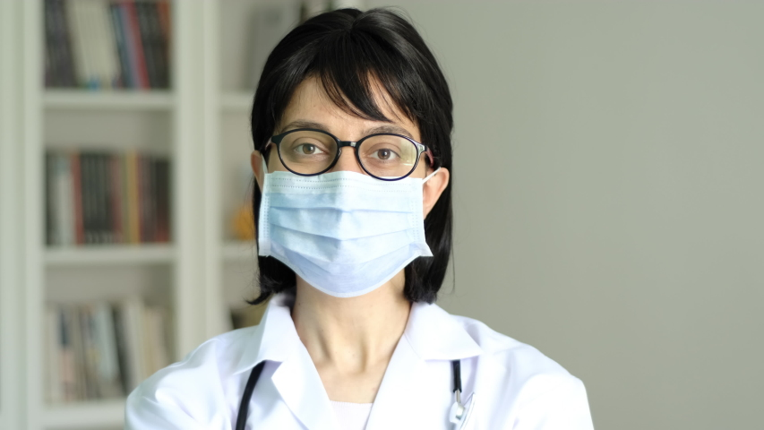 Young adult female doctor wearing face mask close up. Medical protective equipment usage demonstration. Smiling woman portrait. | Shutterstock HD Video #1055246270