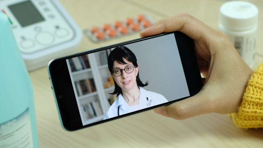 Young adult female doctor talking and smiling on mobile phone. Doctor give advice to patient remote medical consultation. Woman doctor speaking portrait confident and hopeful. | Shutterstock HD Video #1055246279