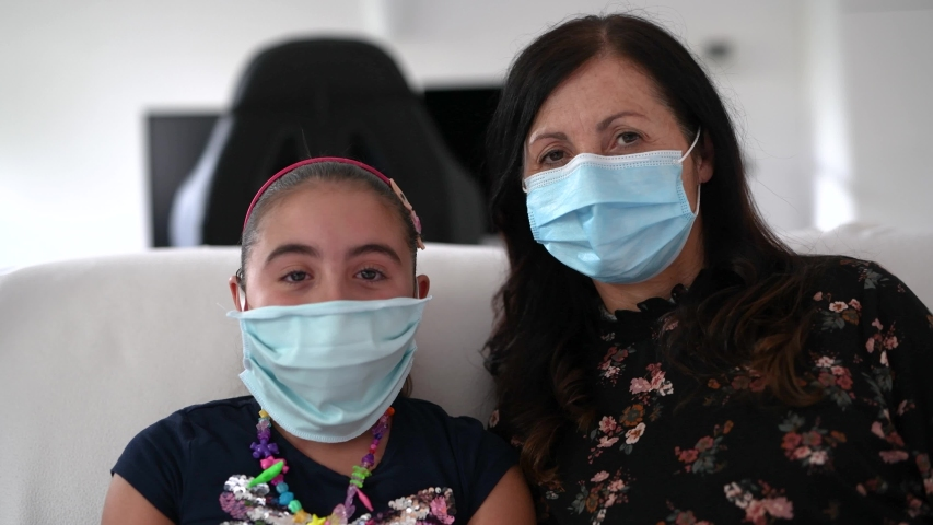 Mother and daughter at home wearing mask, coronavirus concept | Shutterstock HD Video #1055246429