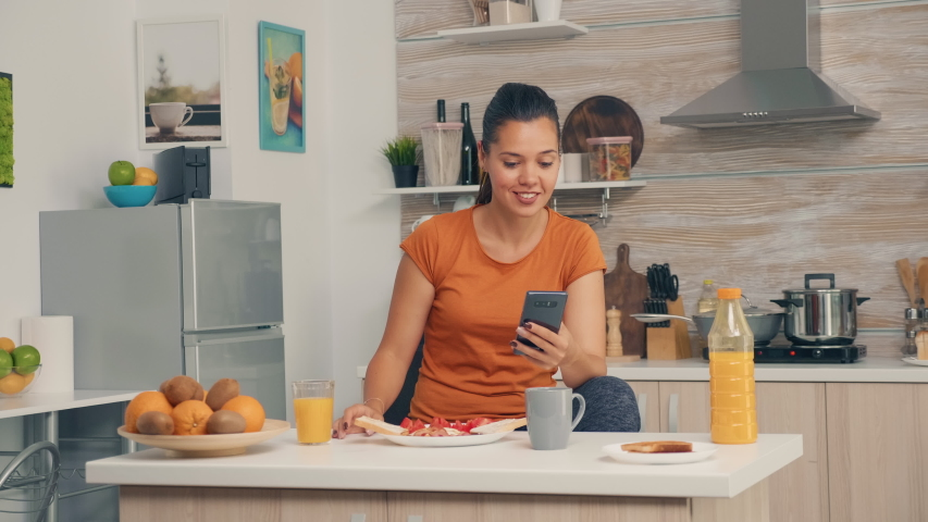 Enjoying a glass of fresh orange juice during breakfast and browsing on smartphone. Woman drinking healthy and natural orange juice. Housewife drinking healthy, natural, homemade orange juice