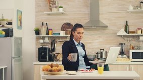 Business woman waving on video call during breakfast. Young freelancer in the kitchen having a healthy meal while talking on a video call with her colleagues from the office, using modern technology