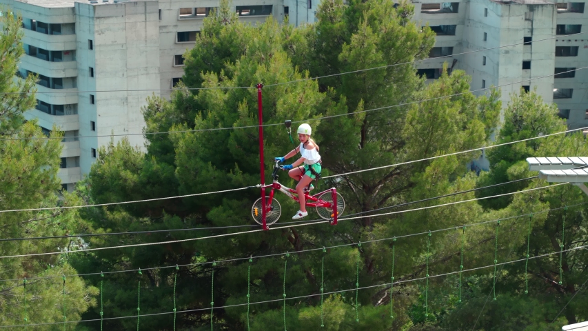 Children in the rope park. Little girl run an obstacle course in a rope park on a rope bicycle. 4k | Shutterstock HD Video #1055248265